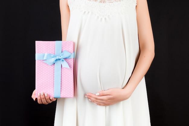검은 배경에 흰색 드레스를 입고 임신 한 여자의 손에 분홍색 발견 선물 상자 닫습니다