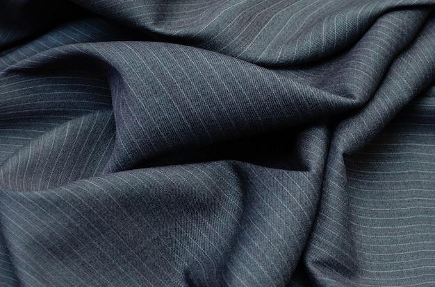 濃い灰色の衣服製造のためのピンストライプ生地テクスチャのクローズアップ。コスチュームファッション用のウールテキスタイル。
