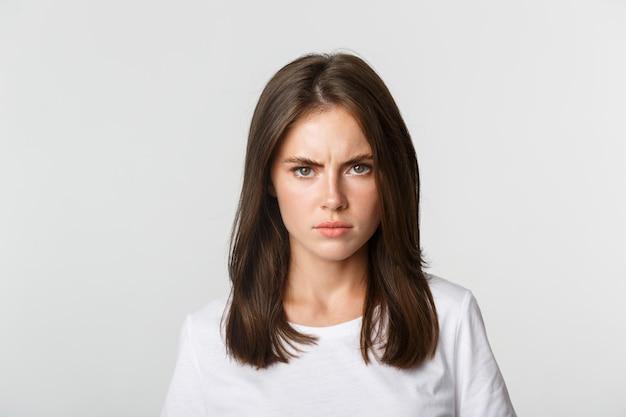 Крупный план рассерженной молодой девушки, хмурящейся и сердито смотрящей в камеру, белый.
