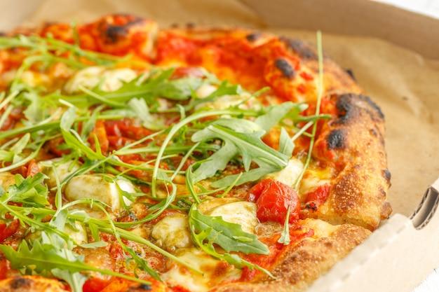 Крупный план пиццы с различными начинками и сыром в картонной упаковке