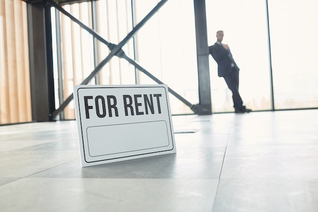 ビジネスマンが背景に立っている空のオフィスビルの床にある賃貸用プラカードのクローズアップ