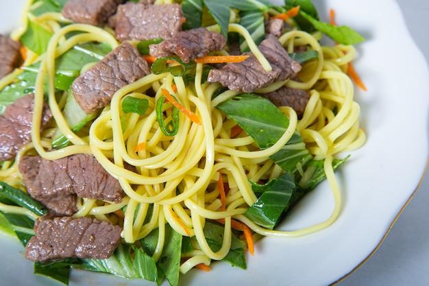 アジアンレストランで牛肉とうどんのプレートのクローズアップ。