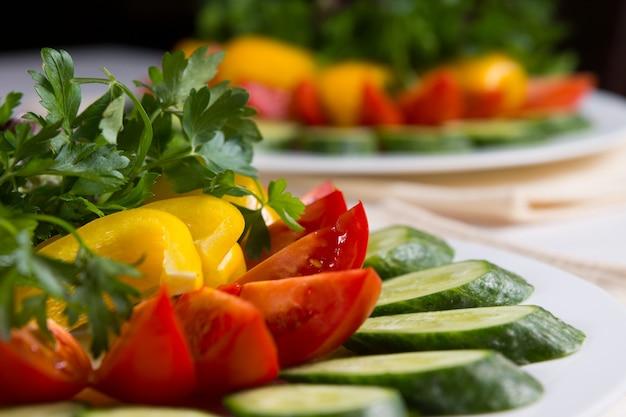 Крупным планом покрытый тарелкой красочный салат с огурцом, помидором и перцем