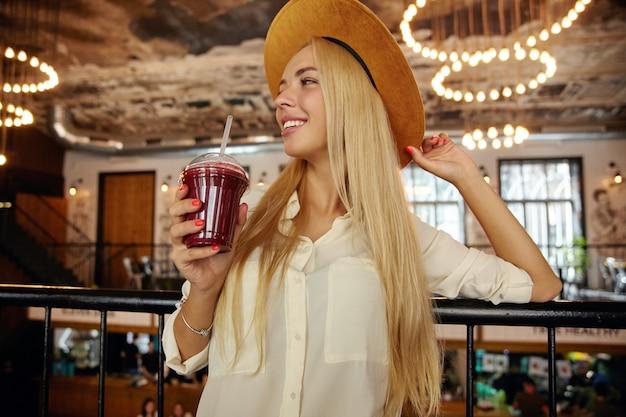 Крупный план приятной на вид длинноволосой блондинки с очаровательной улыбкой, стоящей над интерьером современного кафе в стильной одежде, держа ягодный напиток в поднятой руке