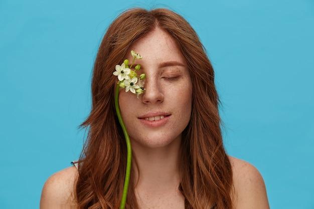目を閉じて青い背景の上に立っている間、彼女の顔に白い花が優しく微笑んでいる気持ちの良い若いポジティブ赤毛の女性のクローズアップ