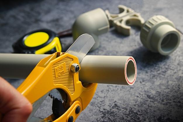 黄色のはさみでpvcパイプを切断する配管工の手のクローズアップ。暖房システムと給水設備。