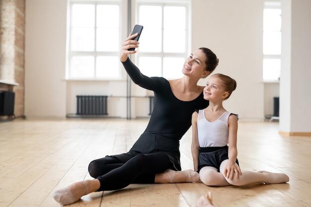 ダンススクールのバックグラウンドで若い女性と少女が互いに話している木の床のトウシューズのクローズアップ
