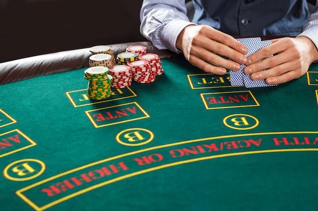 Крупным планом игрока в покер с игральными картами и фишками за зеленым столом казино