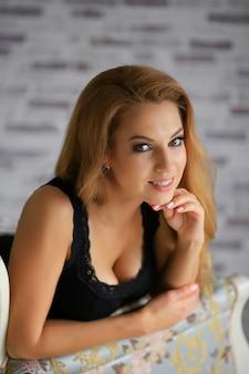 Закройте портрет красивой белокурой девушки улыбается.