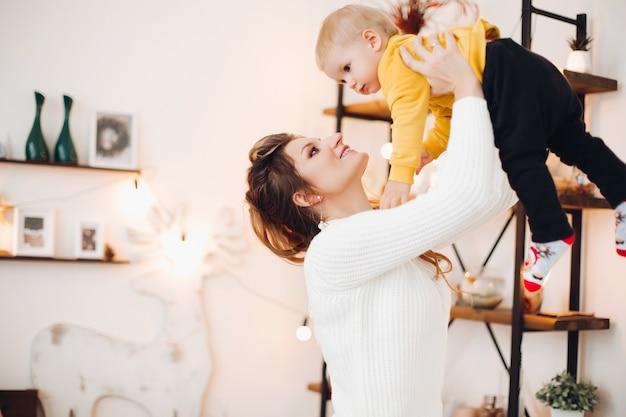 Крупным планом позитивный маленький милый мальчик с красивой мамой в стильно оформленной студии, глядя друг на друга и играя