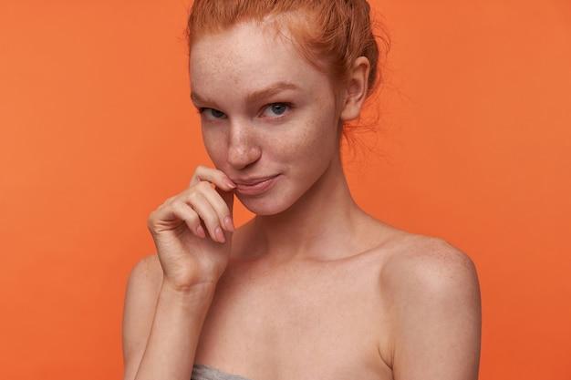 カメラを優しく見て、頬に手を保ち、折りたたまれた唇でオレンジ色の背景の上に立っているカジュアルな髪型のポジティブな恥ずかしがり屋の若いreadhead女性のクローズアップ