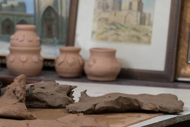 Крупный план гончарной глины на размытом фоне горшков. детские поделки