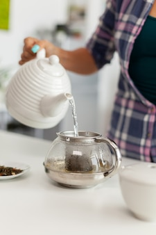 お茶を作るために天然の芳香性のハーブの上にお湯を注ぐのクローズアップ