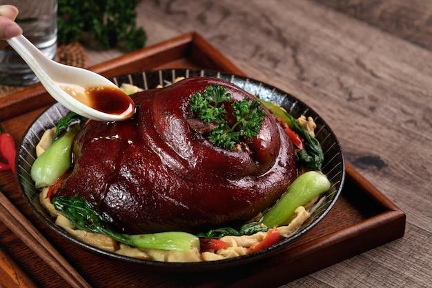 Крупным планом наливание пикантного соевого соуса ложкой на тайваньскую еду, тушеную свинину в тарелке на деревенском столе