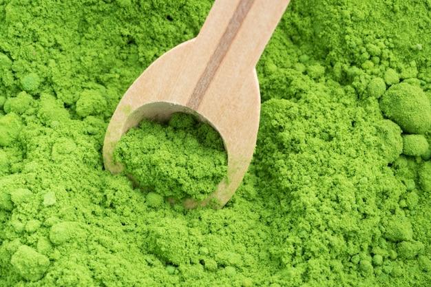 Крупный план порошкового зеленого чая с ложкой woonden