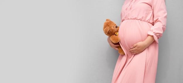テディベアのおもちゃで妊娠中の女性の腹のクローズアップ。妊娠、子育て、準備と期待の概念。