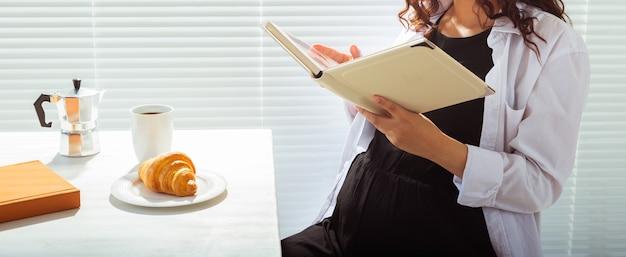 家で本を食べたり読んだりしている妊婦のクローズアップ。朝、朝食、妊娠のコンセプト
