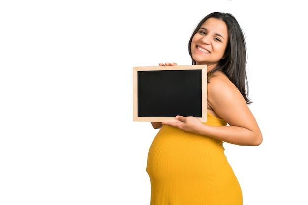 黒板に何かを持って見せている妊婦のクローズアップ。妊娠、母性、プロモーション広告のコンセプト。