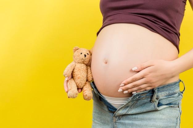복사 공간이 다채로운 표면에 그녀의 배꼽 근처에 테디 베어를 수용하는 압축이 풀린 청바지에 임신 한 여자의 닫습니다