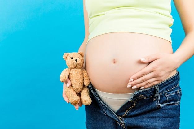 그녀의 배꼽 근처 테디 베어를 수용하는 압축이 풀린 청바지에 임신 한 여자의 닫습니다