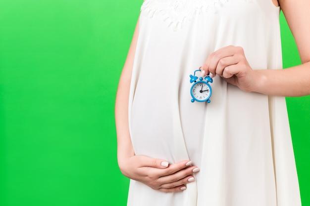 녹색 배경에서 그녀의 배꼽에 알람 시계를 들고 흰 드레스에 임신한 여자의 닫습니다. 출산을 기다리고 있습니다. 공간을 복사합니다.