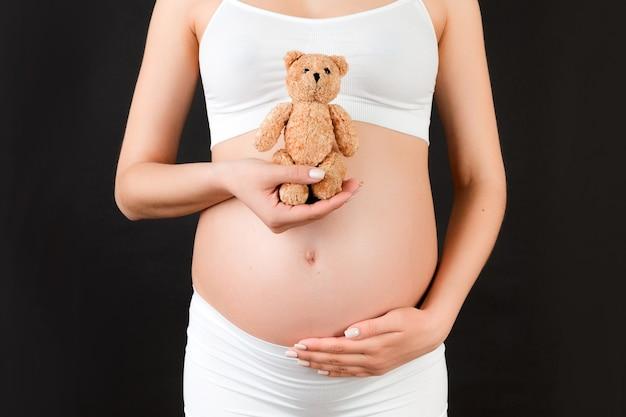 검은 배경에서 그녀의 배꼽에 테디 베어를 들고 흰 속옷에 임신한 여자의 닫습니다. 젊은 어머니는 아기를 기다리고 있습니다. 공간을 복사합니다.