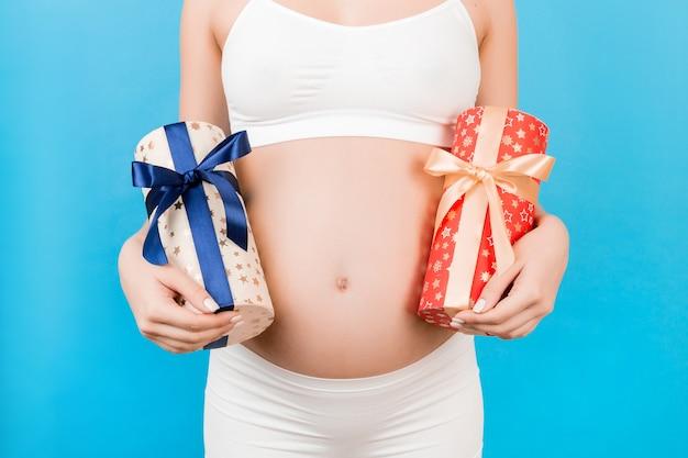 파란색 표면에 두 개의 선물 상자를 들고 흰 속옷에 임신 한 여자의 닫습니다
