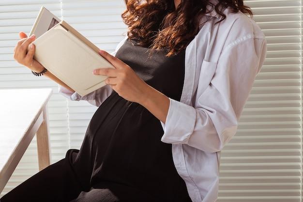 집에서 책을 읽고 임신한 여자의 클로즈업입니다. 아침과 임신 개념
