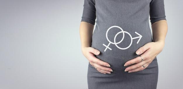홀로그램 남성과 여성의 성별 기호로 임산부의 배꼽을 닫습니다. 임신, 출산 개념입니다.