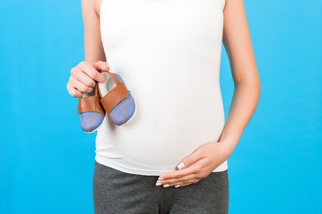 파란색 배경에서 아기를 위한 작은 부츠를 보여주는 임산부의 클로즈업. 미래의 어머니는 아이를 기다리고 있습니다. 공간을 복사합니다.