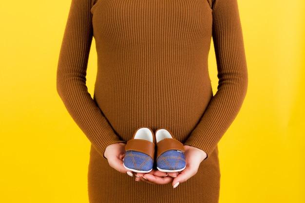 노란색 배경에서 아기를위한 작은 부츠를 보여주는 임신 한 여자의 닫습니다. 미래의 어머니는 아이를 기다리고 있습니다. 공간을 복사하십시오.