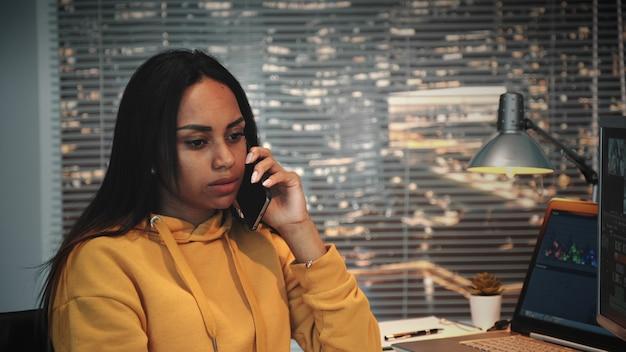 ビデオプロジェクトについてスマートフォンで同僚と話しているかなりアフリカ系アメリカ人のビデオ撮影者のクローズアップ