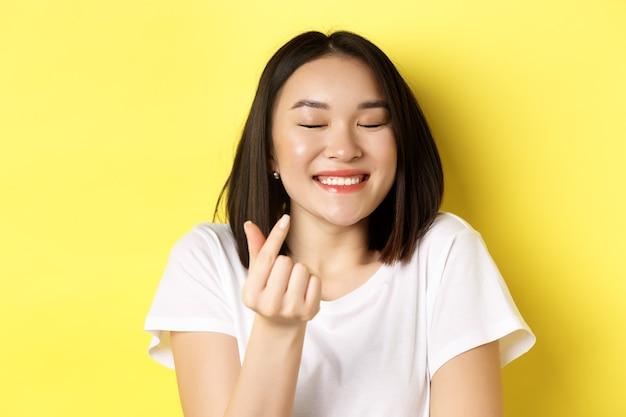 白いtシャツを着たかわいいアジアの女の子のクローズアップ、笑顔で指の心を見せて、私はあなたのジェスチャーを愛し、黄色の上に立っています。