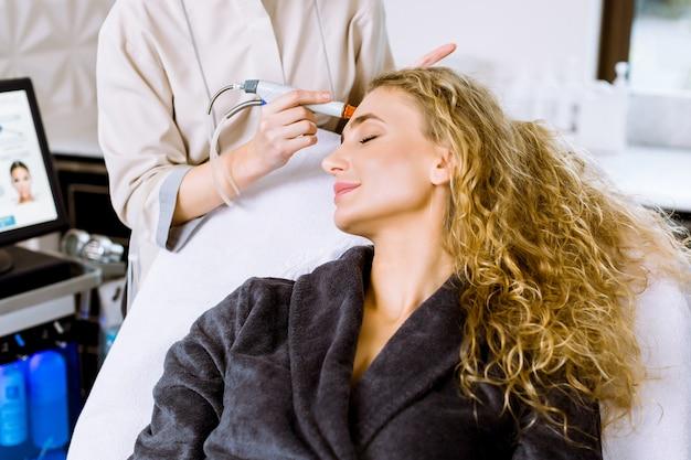 Конец-вверх довольно белокурой женщины получая лицевую обработку шелушения. девушки в косметическом салоне красоты клиники. пылесос hydra.