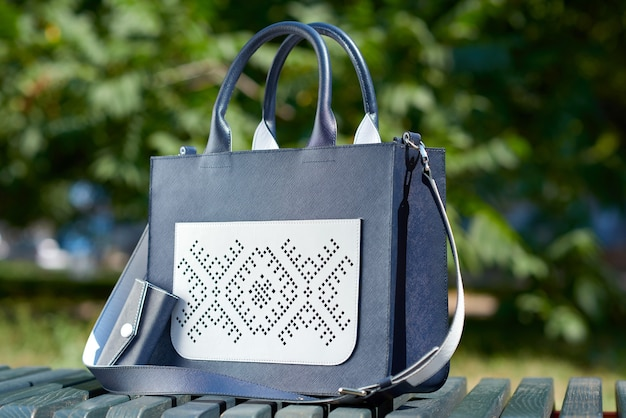 Крупный план довольно модной женской сумки, выполненной в двух цветах: синем и белом. стоит на скамейке в парке. включает ключницу и карман с тиснением. фотография сделана на белом фоне.