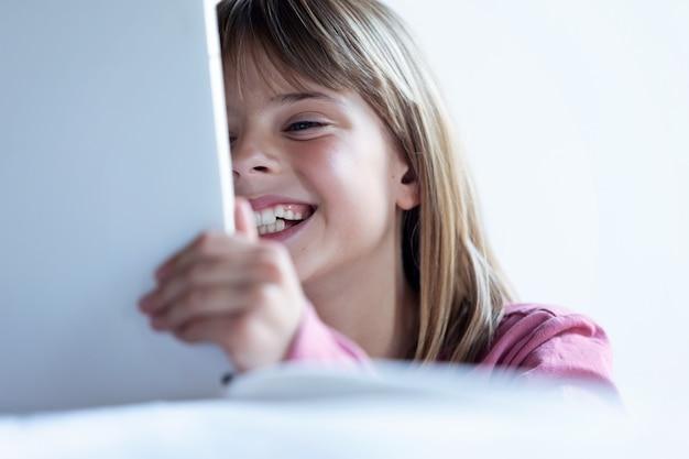 Крупный план довольно счастливой маленькой девочки, использующей ее цифровой планшет дома.