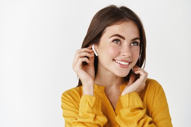 イヤホンで音楽を聴き、ワイヤレスヘッドホンを着用し、笑顔で、白い壁の上に立っているきれいな女性のクローズアップ
