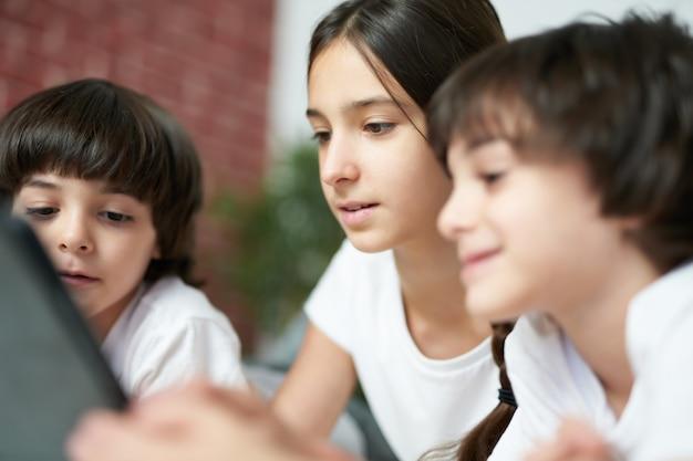 디지털 태블릿을 사용하여 예쁜 10대 라틴계 소녀를 클로즈업하세요. 자매는 집에서 침대에 누워 두 남동생과 시간을 보내고 있습니다. 행복한 어린 시절, 기술 개념