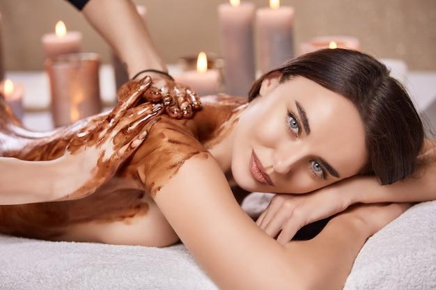 Крупный план красивой женщины, лежащей в спа-салоне и получающей массаж спины с шоколадом