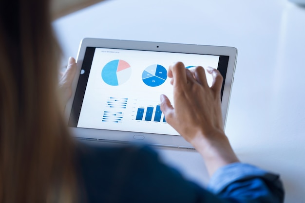 オフィスでデジタルタブレットを使用して作業しているかなり若いビジネスウーマンのクローズアップ。