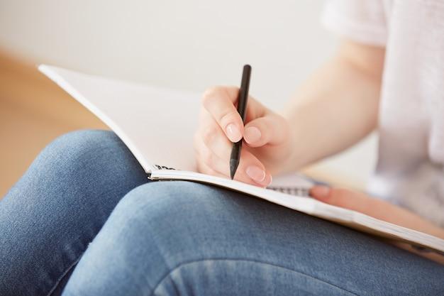 Крупным планом довольно молодая девушка-подросток сидит на полу и делает заметки в своем дневнике