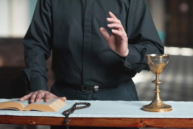 聖書と数珠で祭壇に立っている司祭のクローズアップ