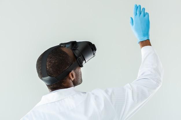 Крупным планом профессионального афро-американского врача, применяющего очки vr