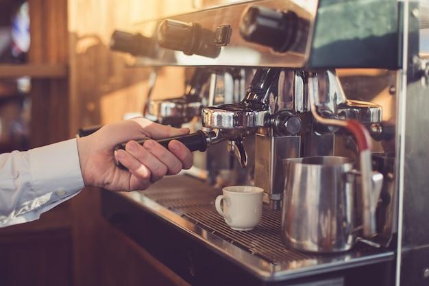 Крупным планом профессионального бариста. мужчина делает кофе с эспрессо-машиной