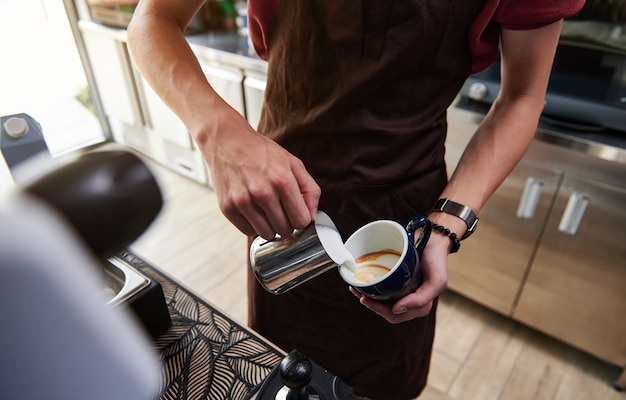 バーカウンターの後ろに美しいラテを作るコーヒーカップに蒸しミルクを注ぐプロのバリスタのクローズアップ