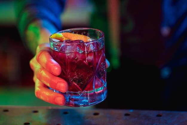 전문 바텐더가 다색 네온 불빛으로 알코올 칵테일 준비를 마치고 고객에게 제공합니다. 엔터테인먼트, 음료, 서비스 개념입니다. 모던한 바, 트렌디한 네온 컬러.