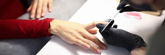 Крупный план профессионального мастера маникюра с помощью пилки для ногтей. свежие и модные процедуры в салоне красоты.