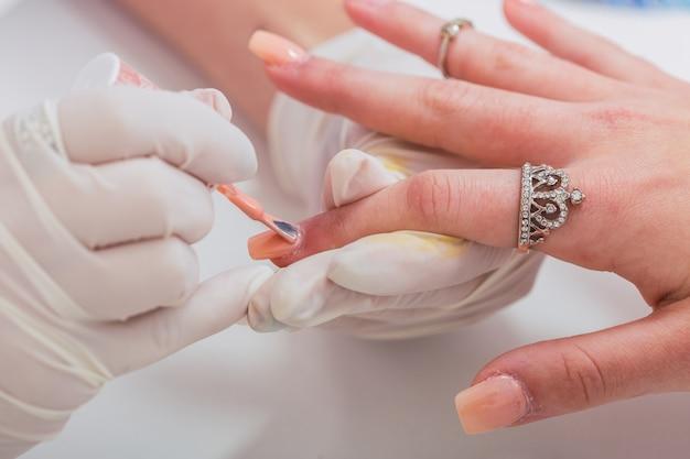 クライアントの手を美化するプロのネイリストのクローズアップ。