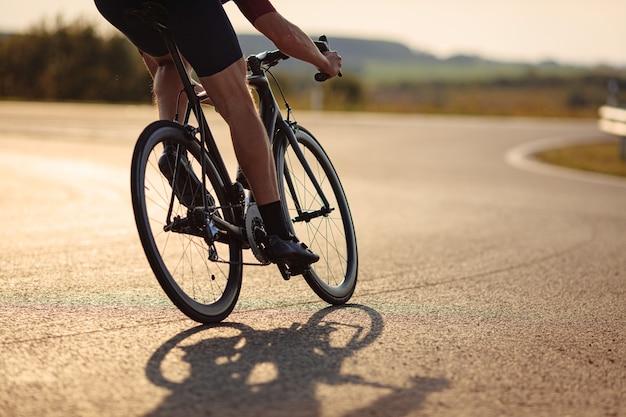 아침 시간 동안 포장 도로에서 자전거를 타는 강한 다리를 가진 전문 도로 자전거 타는 사람의 닫습니다