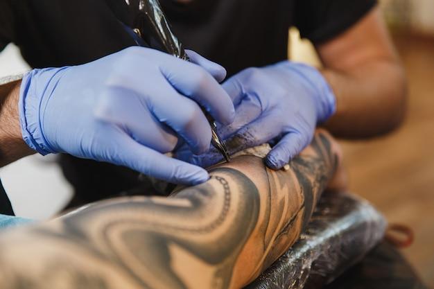 검정 잉크로 기계로 젊은 남자의 팔에 문신을하는 전문 문신 예술가의 닫습니다